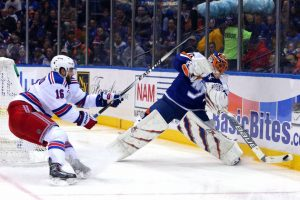 New York Islanders goalie Jaroslav Halak rimming the puck on the boards