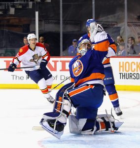 Islanders goalie Thomas Greiss making a glove save against Nick Bjugstad of the Florida Panthers